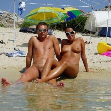Nackte Paare am Strand im Wasser