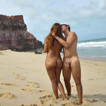 Nackte Paare am Strand küssen